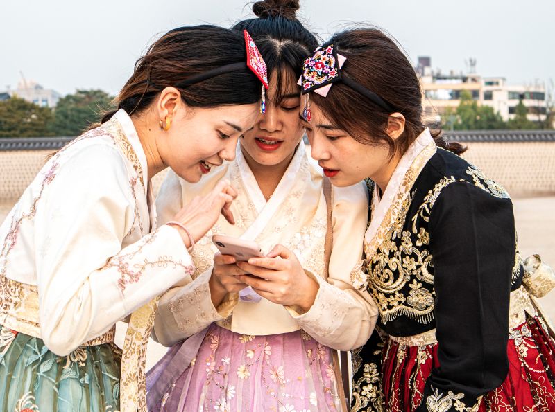 <p>Young girls discuss their pictures taken in traditional Korean robes in front of Changdeokgung Palace, Seoul, South Korea.</p>